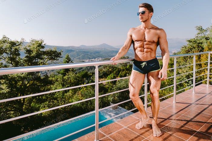 Mode Porträt von einem muskulösen Mann in Badehose bei Schwimmbad