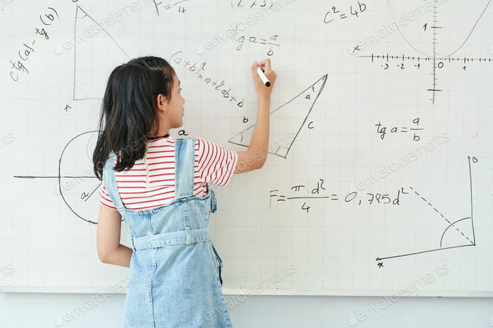 Schoolgirl writing on whiteboard