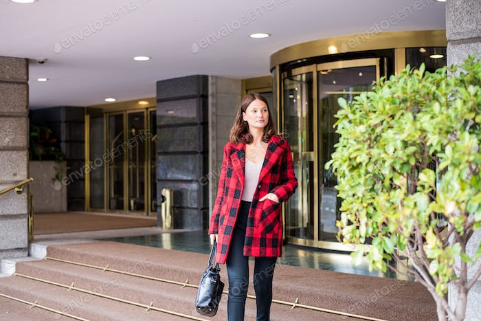 pretty young woman walking leaving an Hotel wearing autumn elegant clothes
