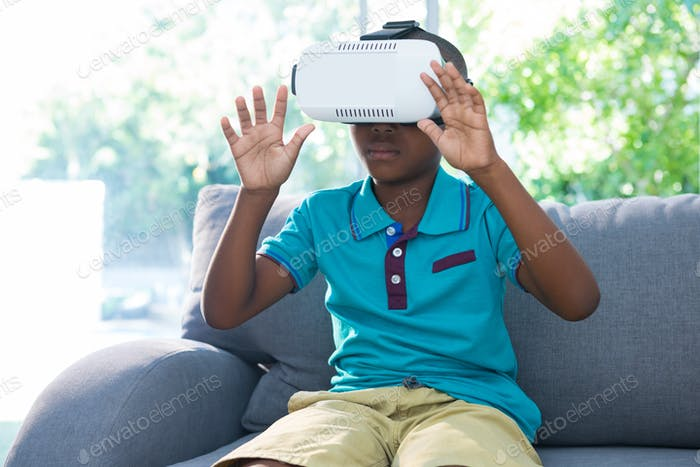 Boy wearing virtual reality headset with arms raised at home