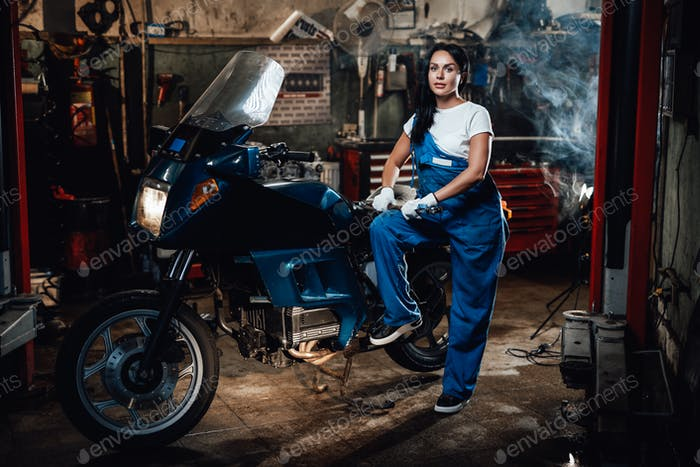 Beautiful brunette woman in blue overalls posing next to a sportbike in garage or workshop