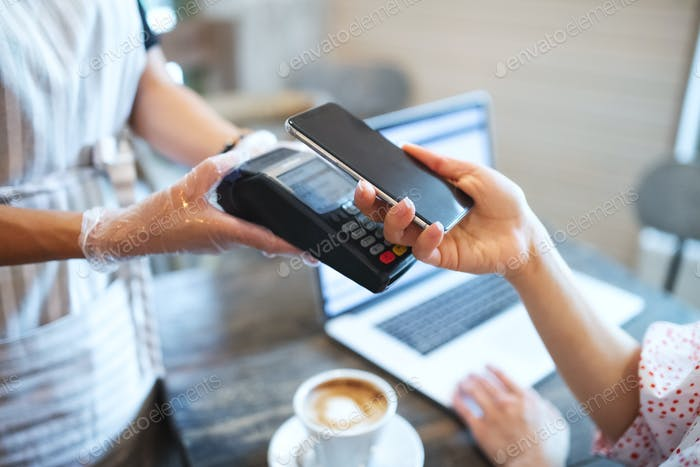 Paying by smartphone in coffee shop after coronavirus lockdown, hygiene concept