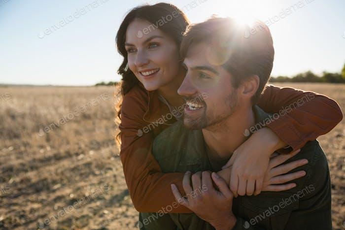 Man giving woman piggyback ride on landscape