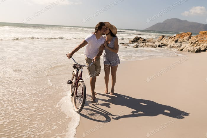 Front view of young woman kissing on man cheek at beach in the sunshine