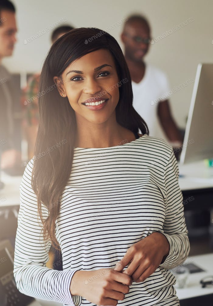 Pretty businesswoman looking at camera in office
