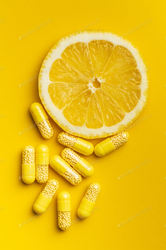 Vitamin capsules. Vitamin C pills and slice of lemon.
