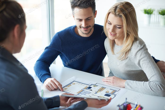 Saleswoman showing paperwork to couple