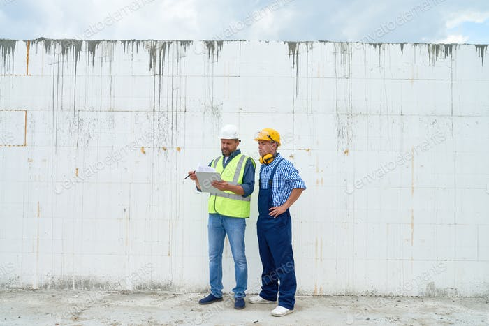 Construction Workers Discussing Building