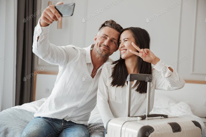 Smiling young couple taking selfie with mobile phone