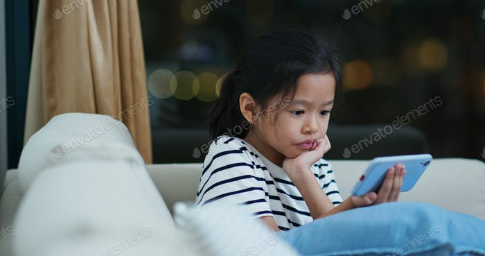 Asian girl watch on mobile phone at home in the evening