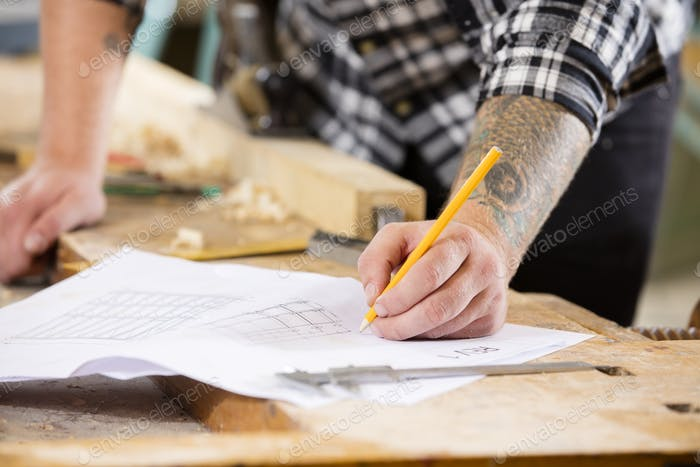 Carpenter plans project and writes at drawings in workshop