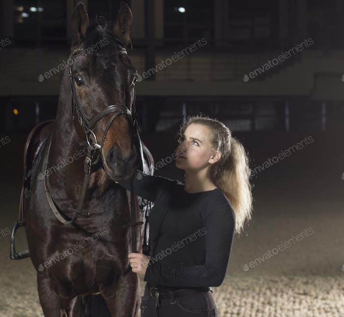 Jockey looking at her beautiful horse