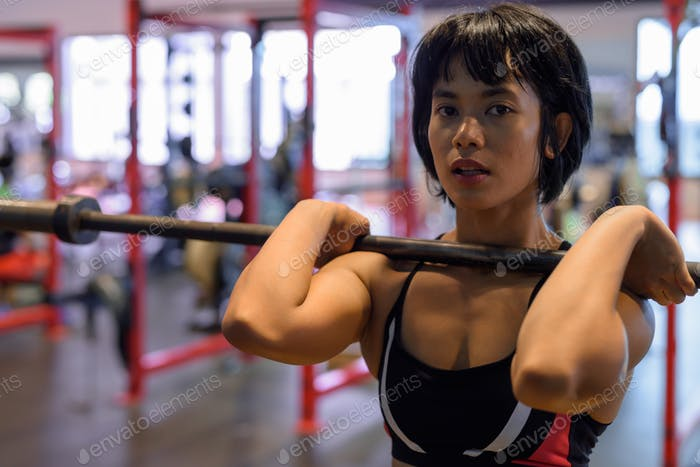 Young beautiful Asian woman working out at the gym