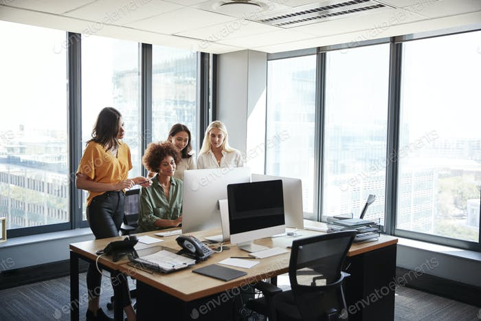 Four female creatives working around a computer monitor in an office, full length view