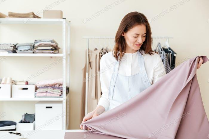 Young woman seamstress looking at fabrics