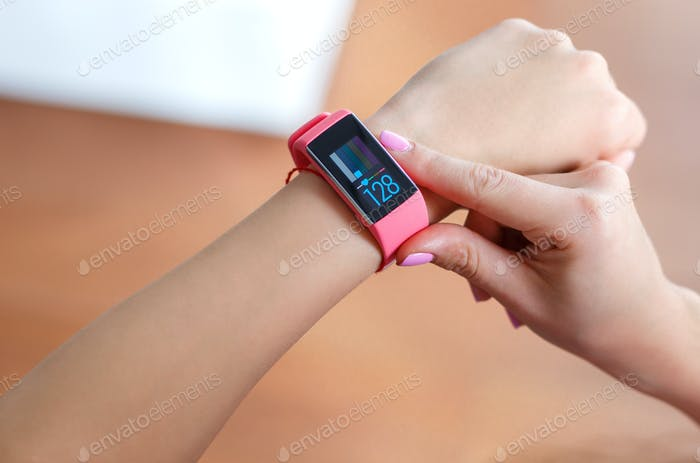 Thumbnail for Isolated female hand with pink smartwatch taking pulse after exercising