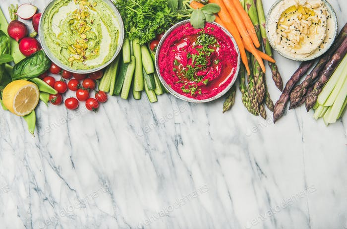 Healthy vegan snack plate with hummus and vegetables, copy space