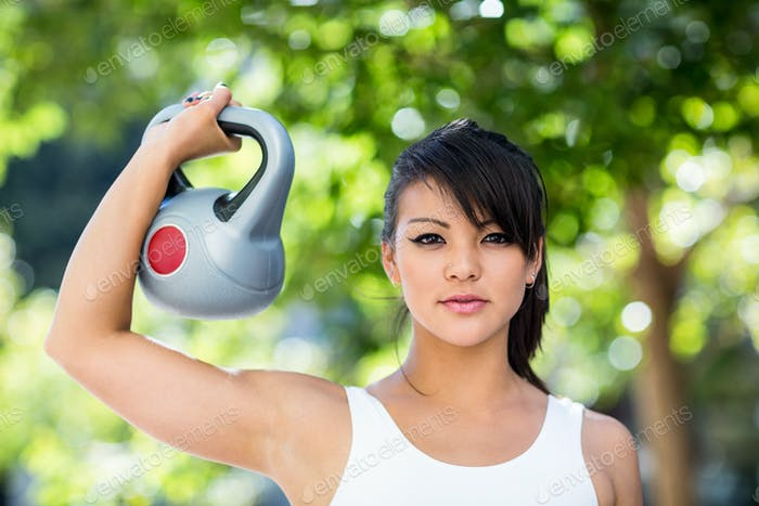 Portrait of athletic woman lifting kettlebell in the city