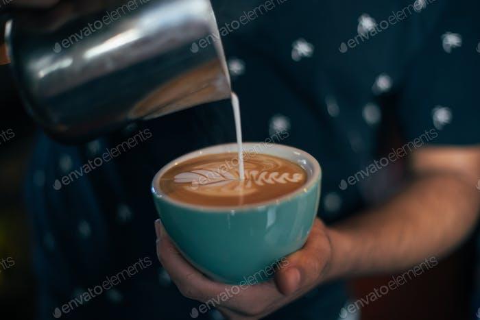 Professional barista draws latte art on coffee cup