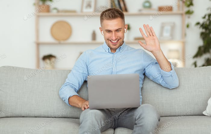 Happy guy using laptop for video call and waving