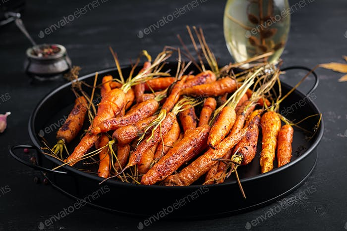 Baked organic carrots with thyme, honey and lemon. Organic vegan food.