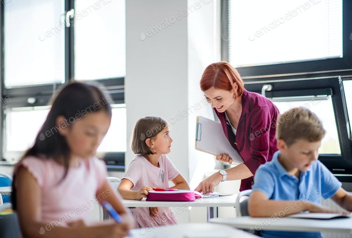 A teacher walking among small school children on the lesson, explaining