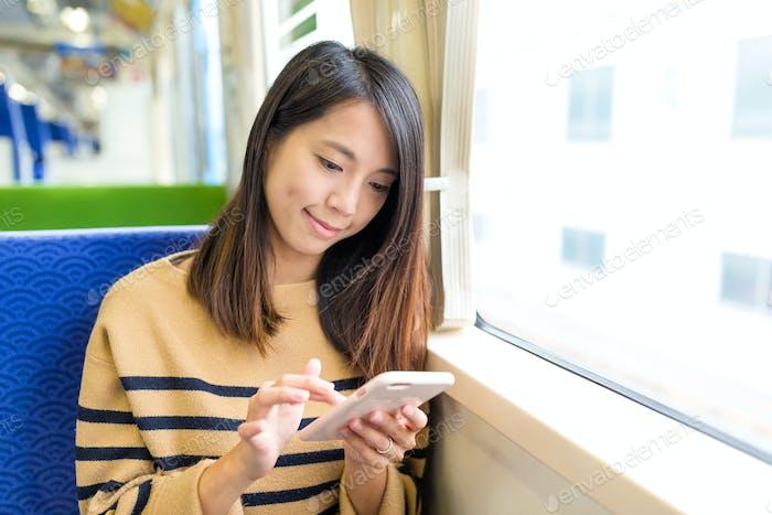 Женщина использование мобильного телефона для онлайн на поезде