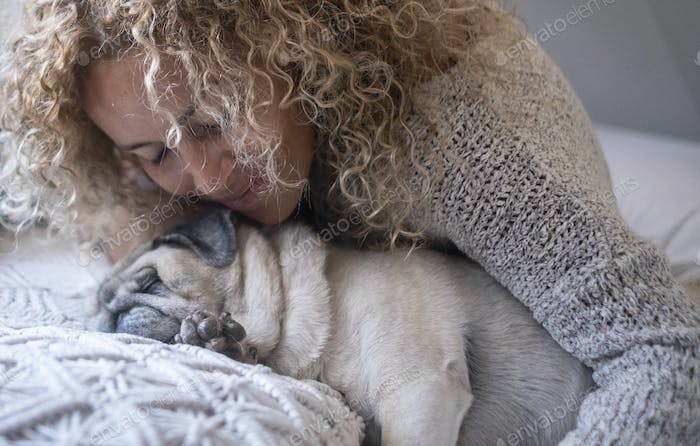 Young woman hugging her pet dog while sleeping on bed. Close up of woman and her dog pug