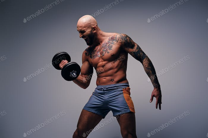 Athletic shaved head male with tattoos on his torso and arms hol