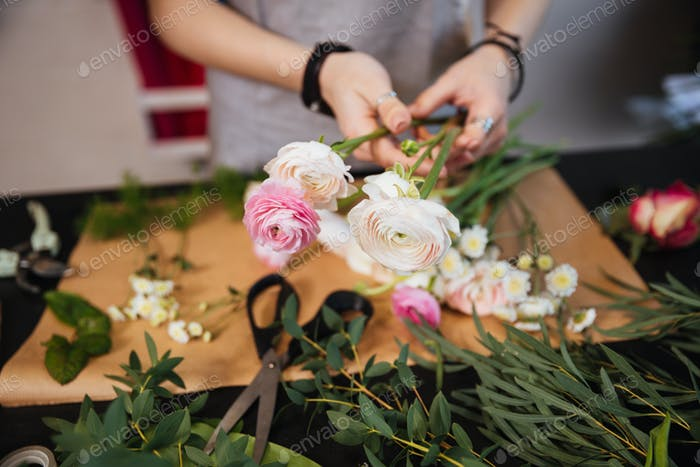 Hands of woman florist creating bouquet with pink roses