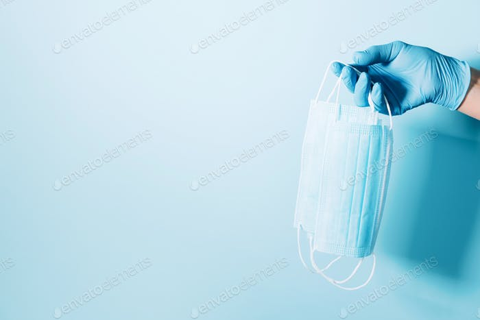 Hand with blue medical gloves holding medical facemask on background. Banner with copy space. Health