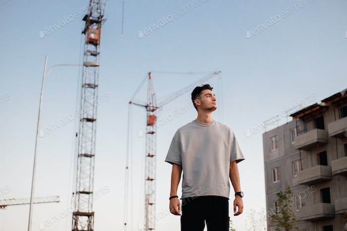 Young guy dressed in jeans and t-shirt is standing next to the building and cranes in the street