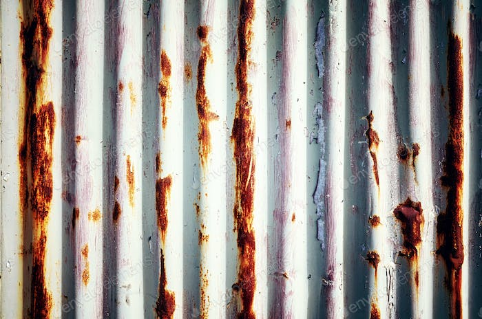 Weathered corrugated rusty metal wall.