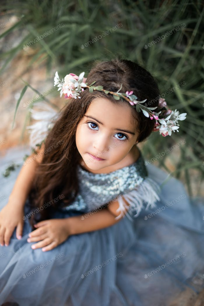 Youth girl with wreath poses on seacoast looking at camera