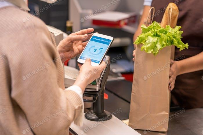 Hands of mature female buyer with smartphone over payment machine