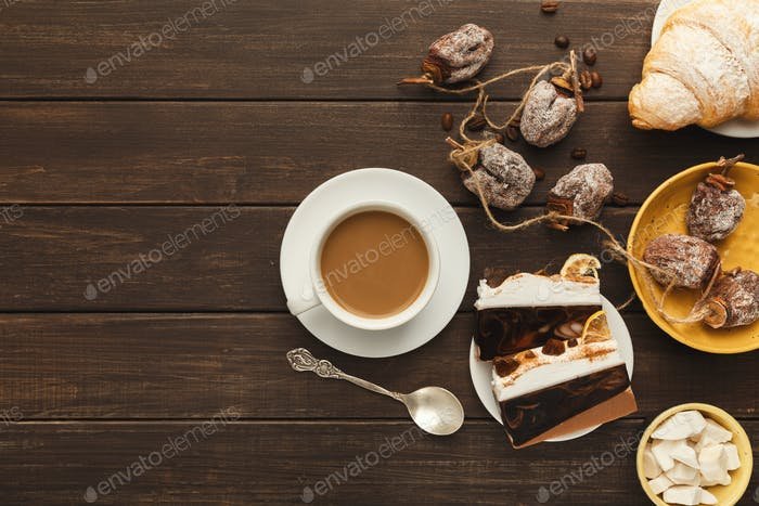 Coffee cup and sweets on vintage wooden table, top view