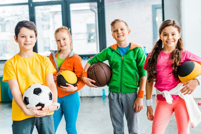 Carefree kids posing with balls in gym
