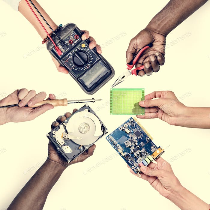 Diverse hands holding computer electronics parts isolated on white