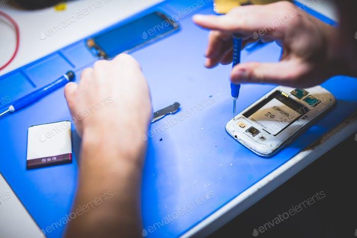 Serviceman fixing broken mobile phone.