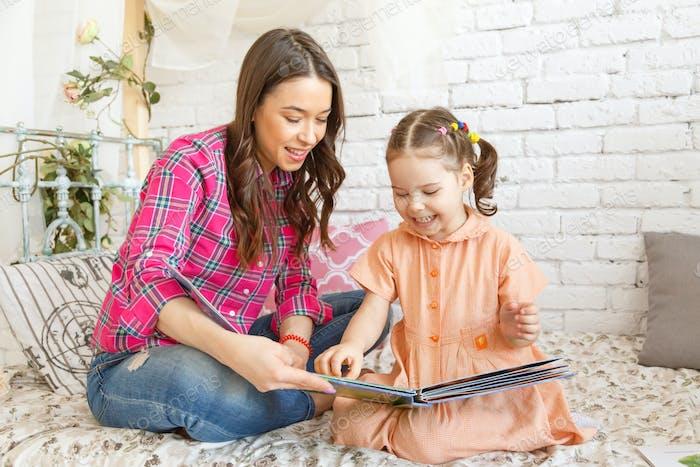 Junge Mutter und ihr Kind Mädchen ein Buch lesen