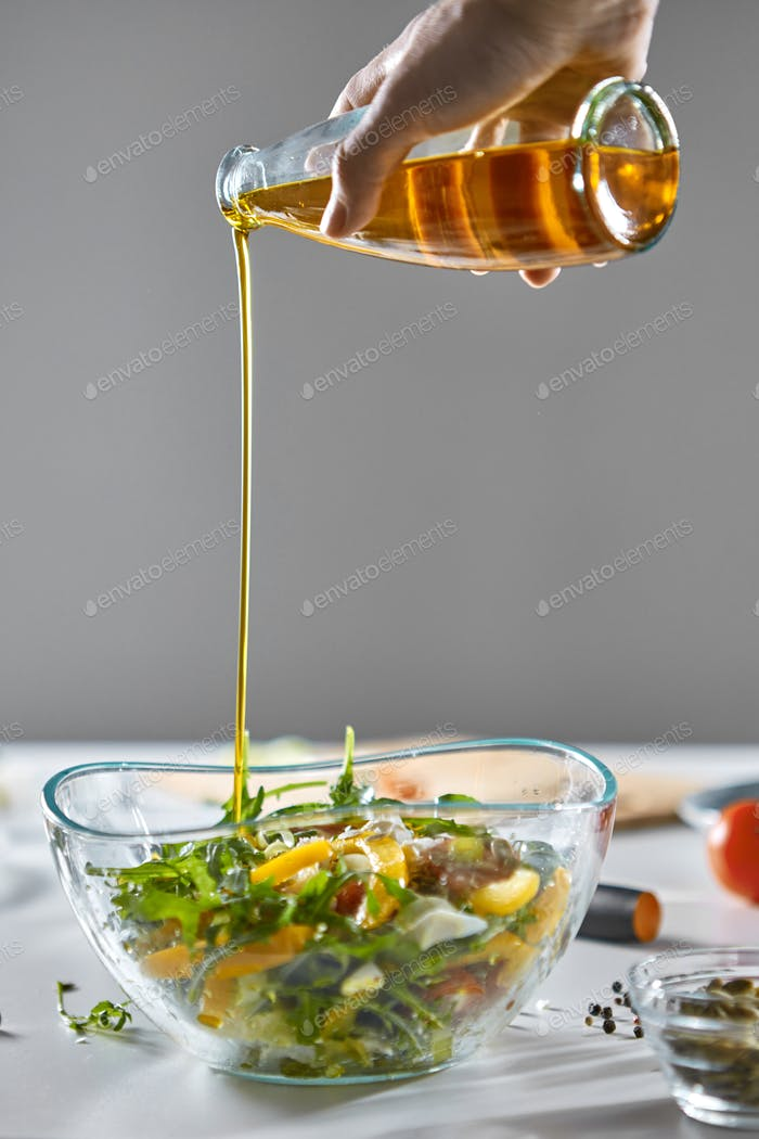 On the kitchen table was a bowl with a healthy salad. A woman's hand pours oil into a salad on a