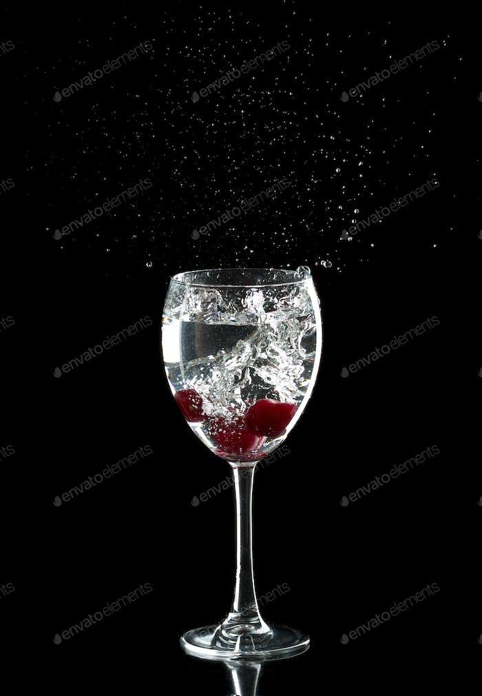 Tres cerezas en un vaso gotas salpicando