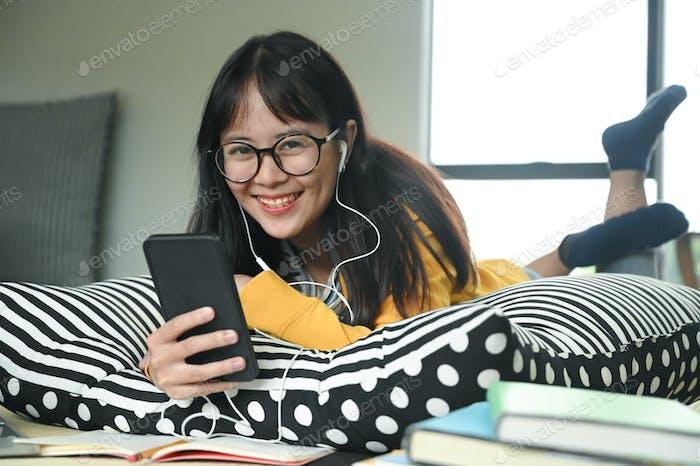 Junge Studentinnen tragen Kopfhörer schlafen auf Kissen Musik von einem Smartphone hören.