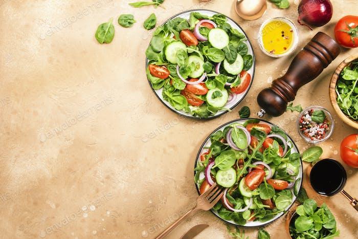 Grüner Frühlingssalat mit Spinat, Kirschtomaten, Maissalat und roten Zwiebeln