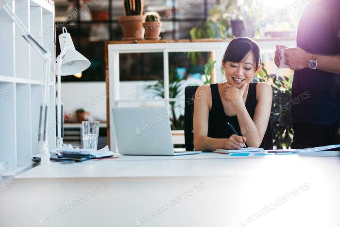 Businesswoman working with colleague standing by