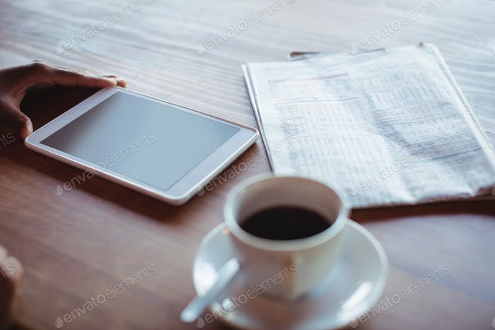 Hand of woman using digital tablet while having coffee