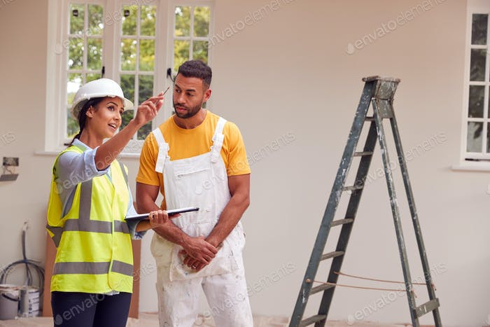 Female Surveyor With Clipboard Meeting With Decorator Working Inside Property