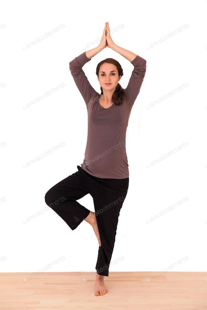 Pregnant Caucasian woman practicing yoga.