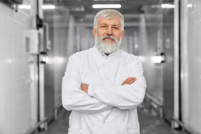 Confident butcher with crossed hands in refrigerator posing