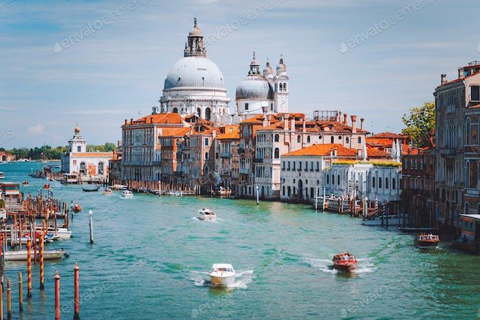 Grand Canal with tourist boats and Basilica Santa Maria della Salute in background, Venice, Italy